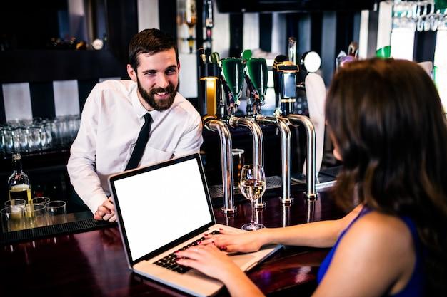Barman talking to customer using laptop in a bar Premium Photo