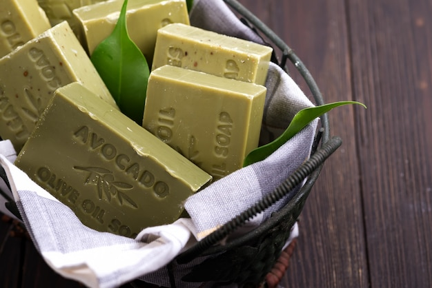 Bars of green natural olive oil soaps with green leaves in a basket on dark wooden Premium Photo