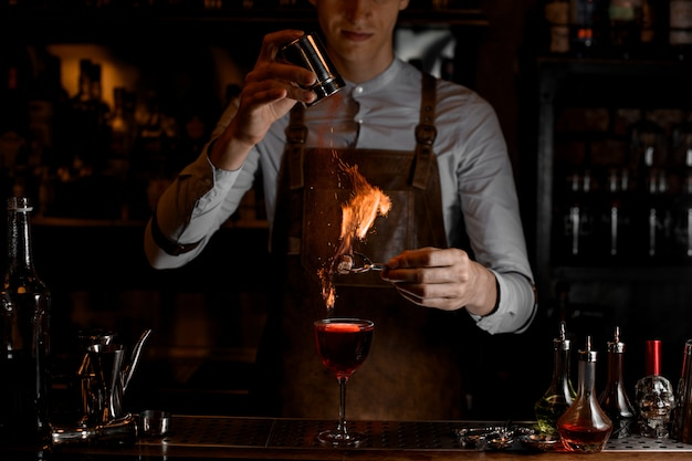 Bartender add spices for a decor in the fire above a delicious red cocktail in the glass Premium Photo