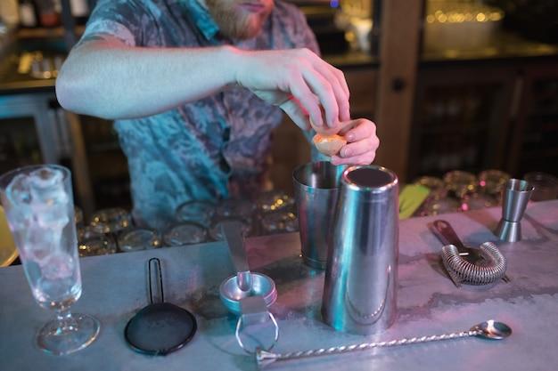 Barista che aggiunge tuorlo d'uovo mentre prepara la bevanda al bancone Foto Gratuite