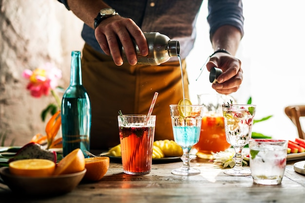 Bartender mixing colorful cocktails Premium Photo