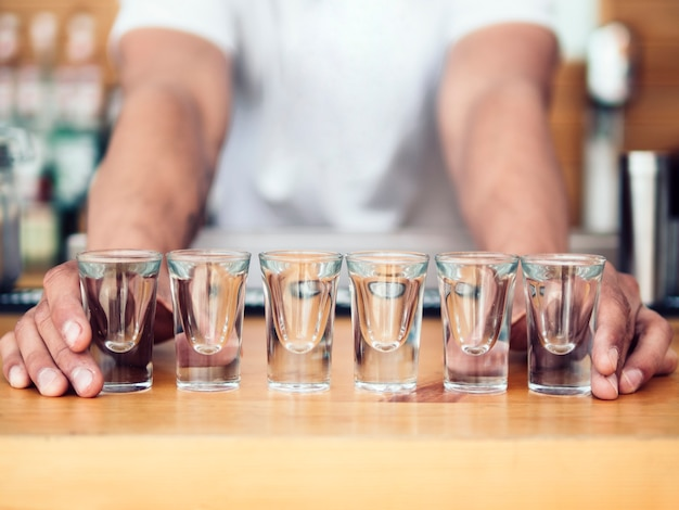 Bartender placing line of shot glasses on counter Free Photo