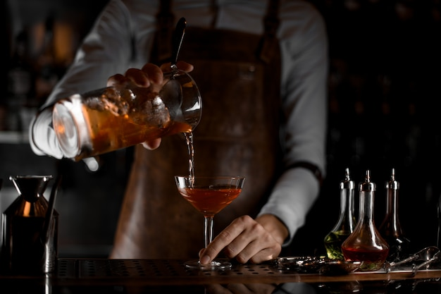 Bartender pouring an alcohol cocktail from strainer Premium Photo