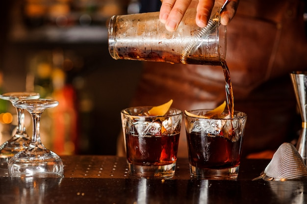 Bartender pouring alcoholic drink into the glasses Premium Photo