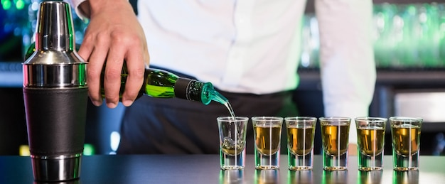 Bartender pouring cocktail into shot glasses at bar counter in bar Premium Photo