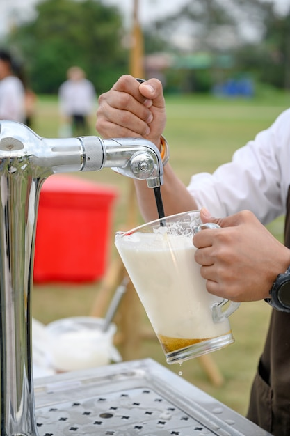 Bartender pouring draft beer from handle tap machine Premium Photo