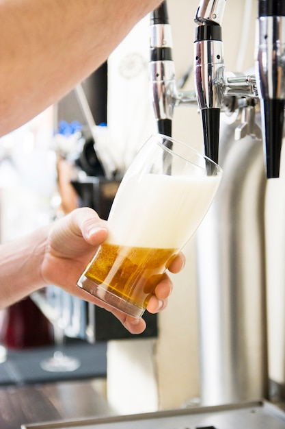 Bartender pouring the fresh beer in pub Free Photo