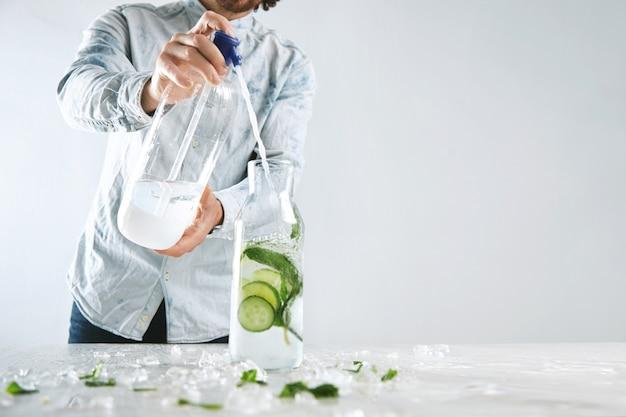 バーテンダーは、ヴィンテージのボトルに氷、キュウリ、ミントをサイフォンから注ぎ、アルコールを含まないモヒートのような寒い夏の健康的な飲み物を作ります 無料写真