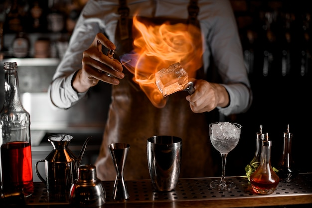Bartender putting a fire on the big ice cube on tweezers above the steel shaker Premium Photo