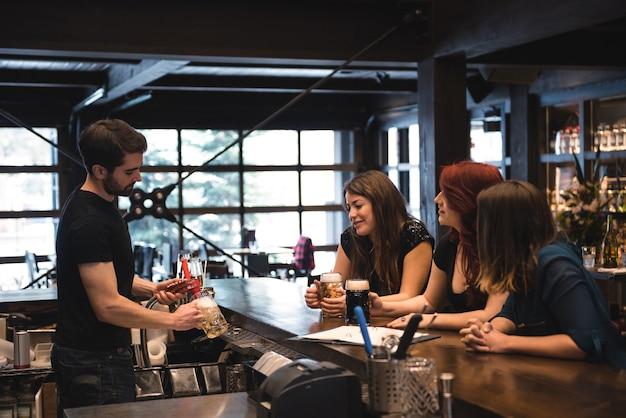 バーカウンターでビールを提供するバーテンダー 無料写真