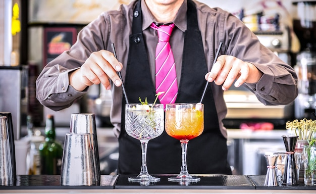 Bartender serving gin tonic and tequila sunrise at cocktail bar Premium Photo