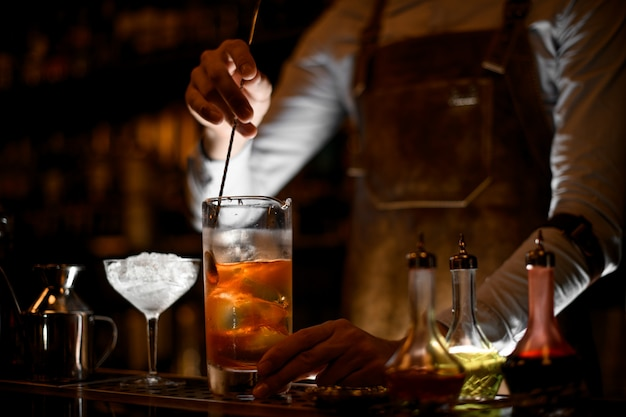 Bartender stirring alcohol cocktail with the spoon Premium Photo