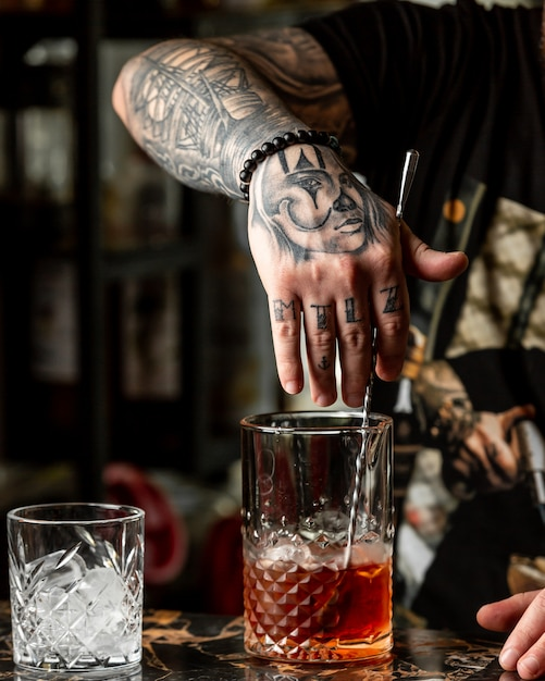 Bartender with tattoos making a red cocktail with whiskey. Free Photo