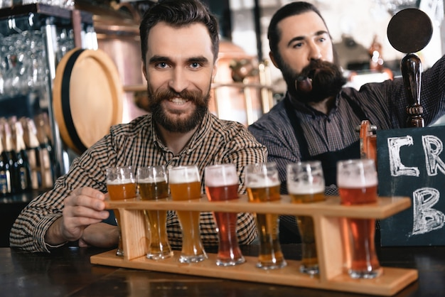 Bartenders pour fresh beer into glasses in pub Premium Photo