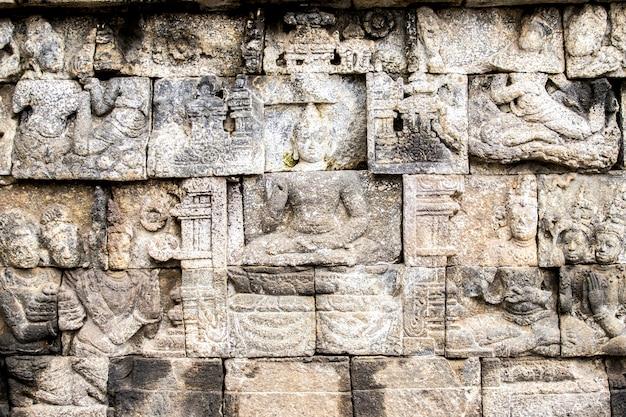 Bas-relief sculptures on wall at borobudur temple, yogyakarta, java island, indonesia Premium Photo