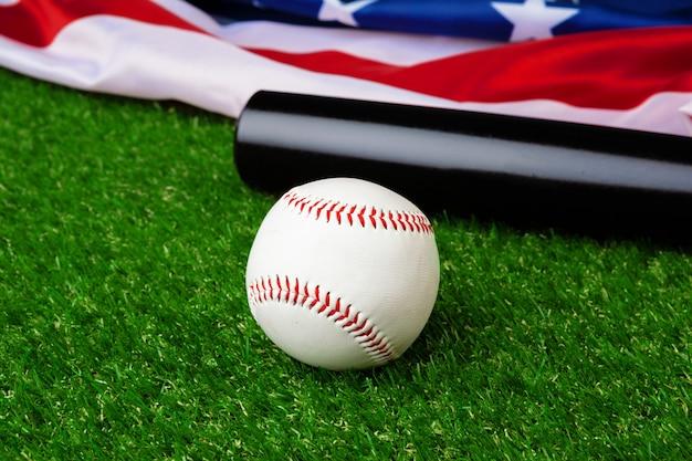 Baseball bat and ball with american flag on grass Premium Photo