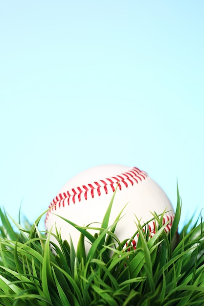 Baseball in grass on blue Free Photo