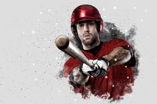 Baseball player with a red uniform coming out of a blast of smoke . Premium Photo