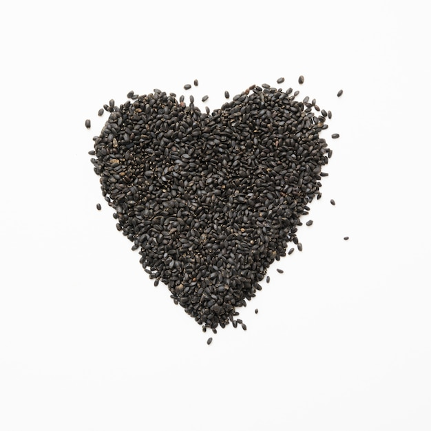 Basil seeds in shape of heart on white. square image. Premium Photo