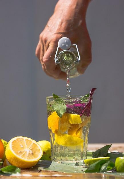 Алкогольный коктейль basil smash gin со свежими листьями базилика и цитрусовыми. напиток в замораживающем движении, капли в брызгах жидкости, струя сока, ломтик лайма в полете. летний холодный напиток Premium Фотографии