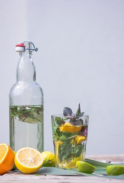 Алкогольный коктейль basil smash gin со свежими листьями базилика и цитрусовыми. Premium Фотографии