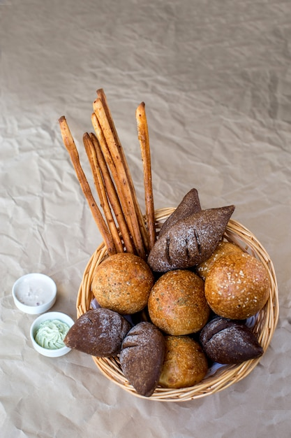 A basket of bread buns with brown, spicy breads and bread sticks Free Photo