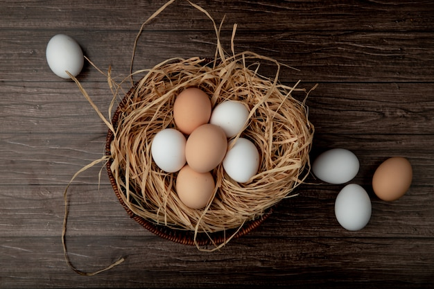 Basket of eggs in nest with eggs around on wooden table Free Photo