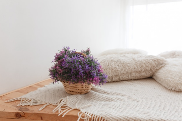 Basket of jute with purple flowers wooden floor with knitted pillows and covering Free Photo