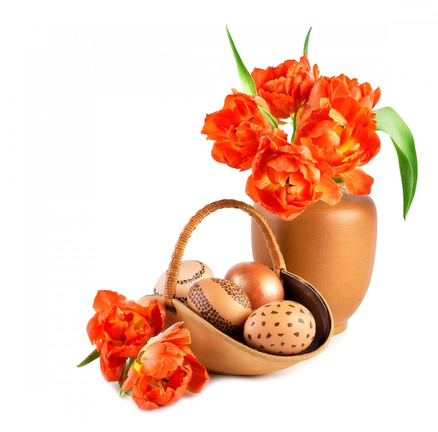 Корзина пасхальных яиц и букет оранжевых тюльпанов в фарфоровой вазе Premium Фотографии