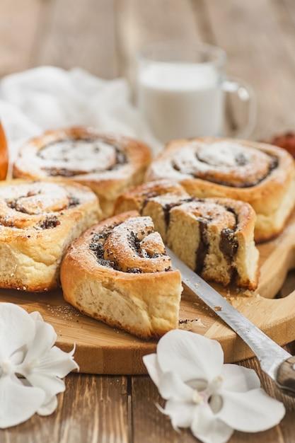 Корзина домашних булочек с вареньем, подается на старом деревянном столе с грецкими орехами и чашкой молока Premium Фотографии