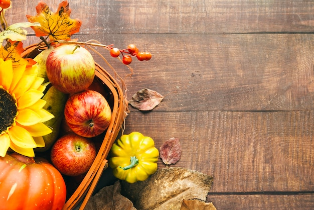 Basket with autumnal harvest and sunflower on table Free Photo
