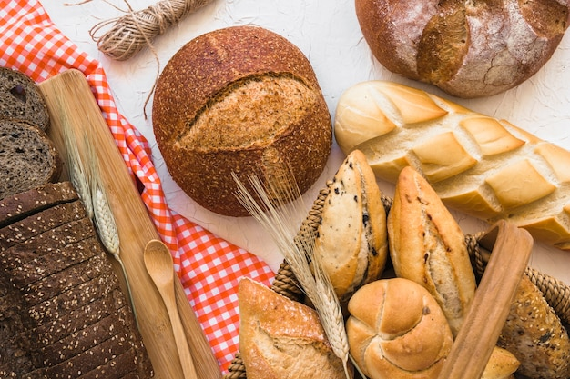 Basket with buns near loaves of bread Free Photo
