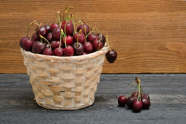 Basket with cherries on a wooden table. copy space Premium Photo