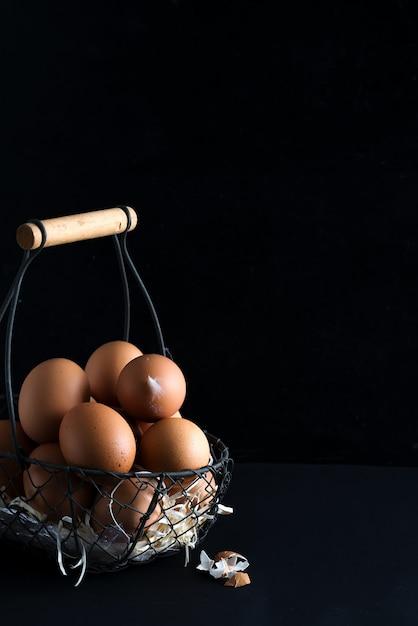 Basket with close up fresh farm natural chicken eggs on a black background. farm eco friendly Premium Photo