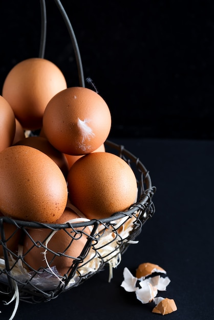 Basket with close up fresh farm natural chicken eggs on a black background. farm eco friendly Premium Photo