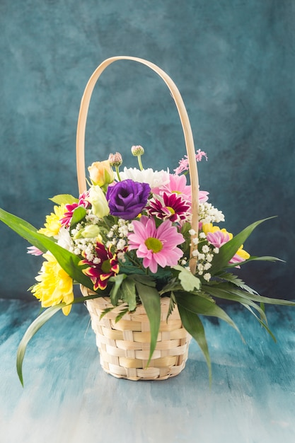 Basket with different flowers placed on desk Free Photo