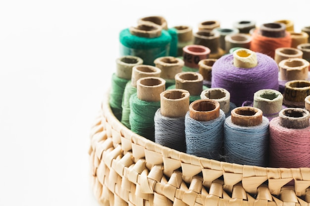 Basket with sewing threads on white background Free Photo