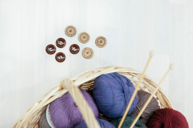 Basket with a variety of wood of yarns, knitting needles and buttons Premium Photo