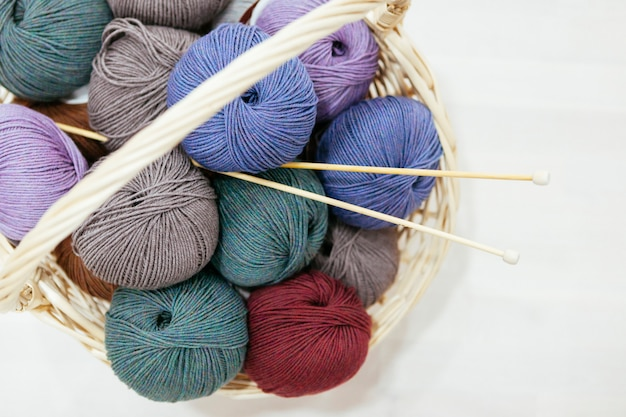 Basket with a variety of wood of yarns and knitting needles Premium Photo