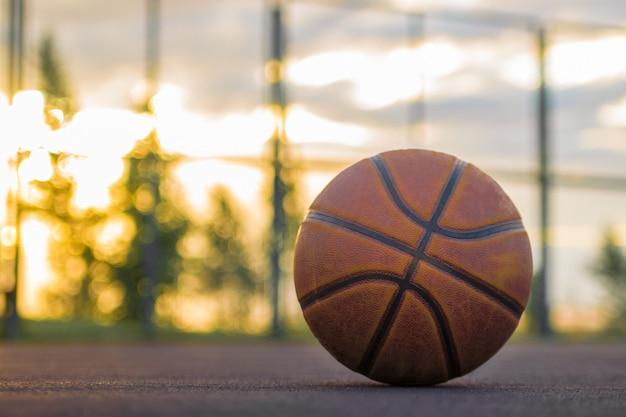 Баскетбольный мяч лежит на земле на фоне вечернего неба. спортивный фон Premium Фотографии