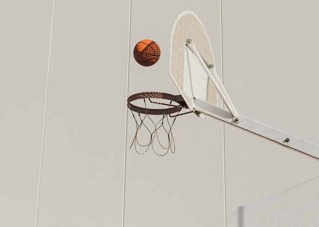 Basketball falling in hoop against wall Free Photo