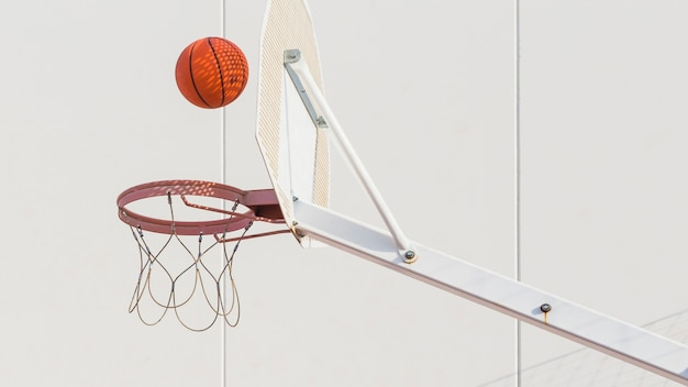 Basketball falling in hoop Free Photo