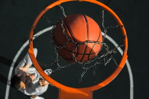 Basketball falling through ring close up Free Photo