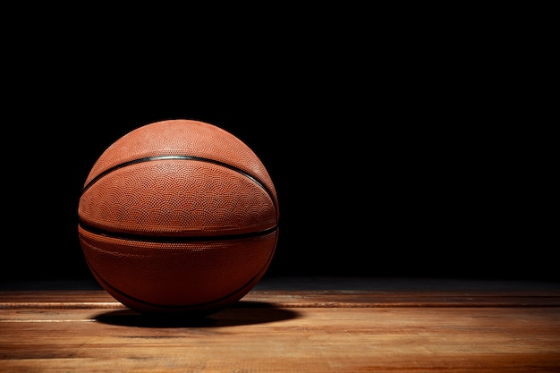 Basketball on a hardwood court floor Free Photo