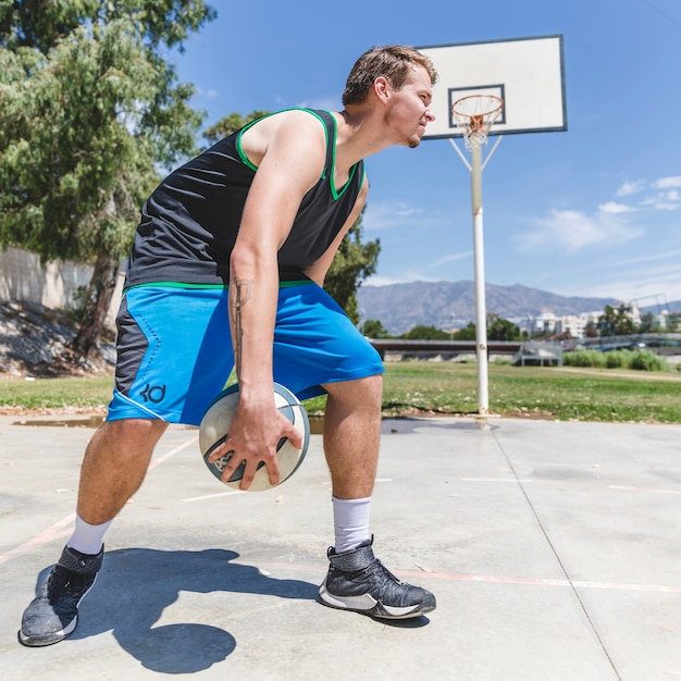 A basketball player holding ball at outdoors court Free Photo
