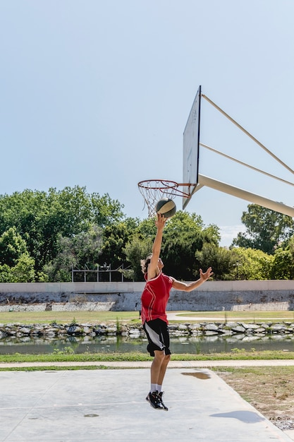 Basketball player throwing ball in the hoop at outdoors court Free Photo
