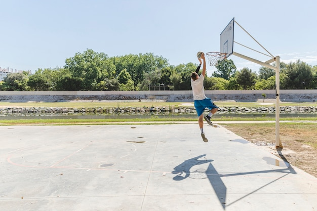 Basketball player throwing basketball in the hoop Free Photo