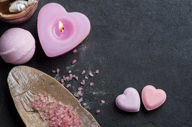 Bath bomb closeup with pink lit candle Premium Photo