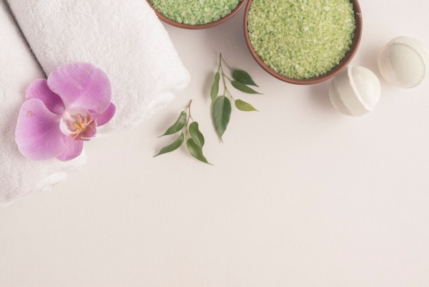 Bath bombs, herbal sea salt and rolled up towels with orchid on white backdrop Free Photo