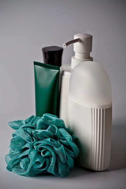 Bath cosmetic products: liquid soap, bath foam, creme and turquoise sponge Premium Photo